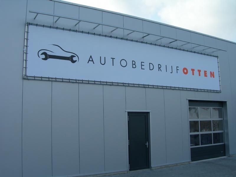 Auto bedrijf Otten Spandoek in buisframe aan pand